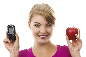 Happy woman holding glucometer and fresh apple.